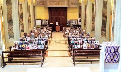 Il don dice Messa con le foto dei suoi fedeli sulle panche
