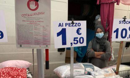 Al mercato gli ambulanti espongono i volantini contro la violenza sulle donne
